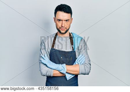 Young hispanic man wearing apron with arms crossed skeptic and nervous, frowning upset because of problem. negative person.