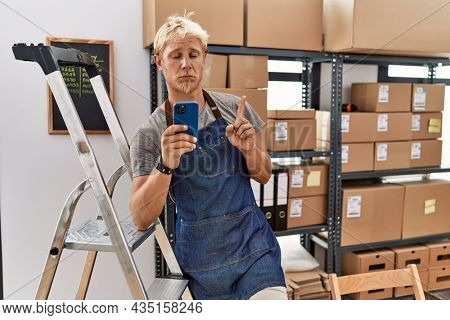 Young blond man using smartphone working at storehouse pointing up looking sad and upset, indicating direction with fingers, unhappy and depressed.