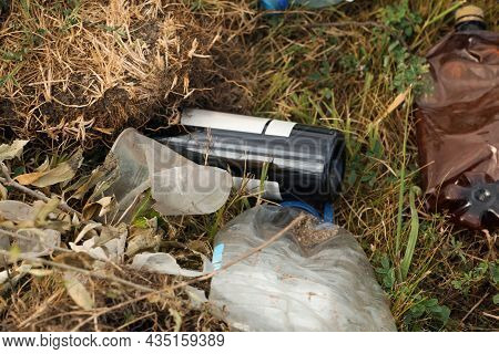 Garbage Scattered On Grass. Environment Pollution Problem