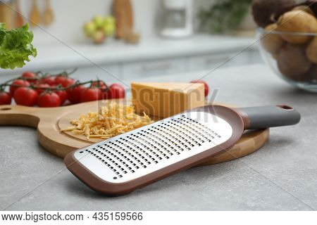 Grater And Cheese On Grey Table In Kitchen