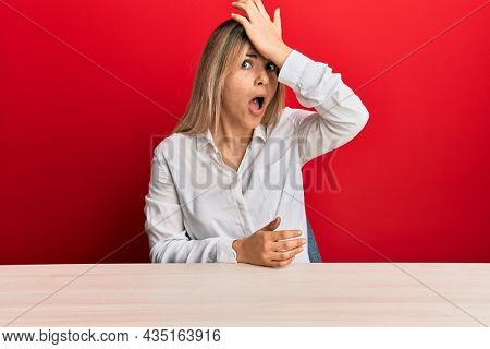 Young caucasian woman wearing casual clothes sitting on the table surprised with hand on head for mistake, remember error. forgot, bad memory concept.