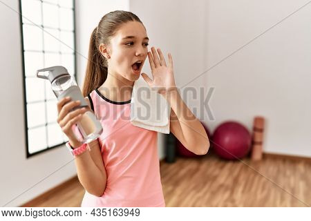 Young brunette teenager wearing sportswear holding water bottle shouting and screaming loud to side with hand on mouth. communication concept.