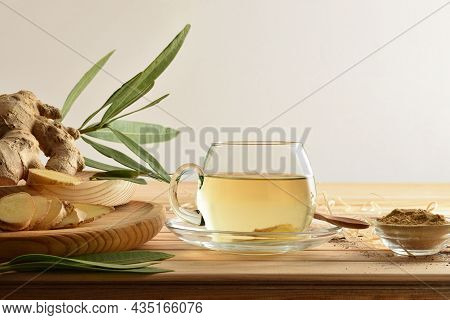 Organic Ginger Infusion On Wooden Table With Root Ginger Powder, Leaves, Straw And Soil And White Is