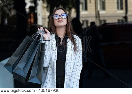 Young Girl Shopper With Shopping Bags In Hand On Black Background. Black Friday, Sale, Discount.