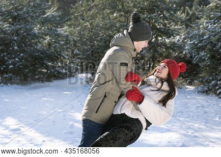 Loving Couple Have Fun In Winter In Forest. Walk On Frosty Clear Day