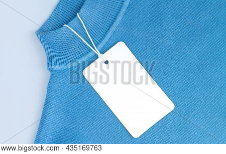Mock-up Of Blank White Paper Price Tag Or Label On Blue Jersey Background Close-up