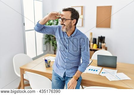 Middle age hispanic man with beard wearing business clothes at the office very happy and smiling looking far away with hand over head. searching concept.