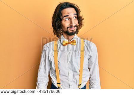 Young hispanic man wearing hipster elegant look smiling looking to the side and staring away thinking.