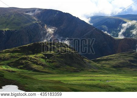 Dawn In The Altai Mountains At The Karagem Pass In Summer, Huge Rocky Mountains With Light Clouds Be
