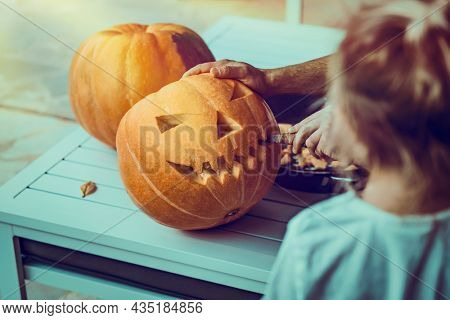 Father and Little Son Preparing for Halloween Holiday. Carved Face on a Pumpkin. Making Traditional Jack-o-Lantern. Spending Time Together.