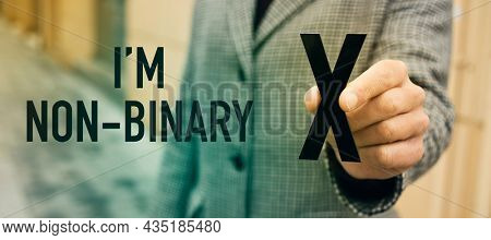 a young caucasian person standing on the street showing an X, for the third gender category, and the text I am not binary, in a panoramic format to use as web banner or header