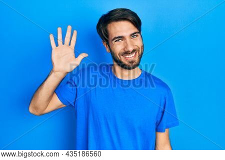 Young hispanic man wearing casual clothes waiving saying hello happy and smiling, friendly welcome gesture