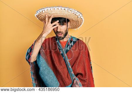 Young hispanic man holding mexican hat surprised with hand on head for mistake, remember error. forgot, bad memory concept.