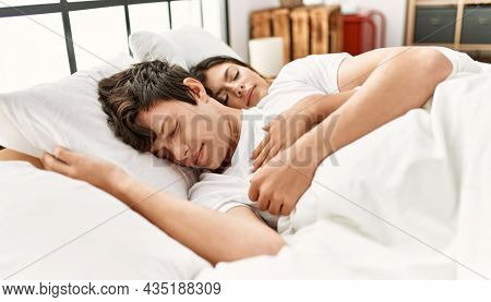 Young caucasian couple sleeping lying on the bed at home.