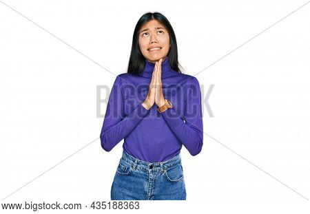 Beautiful young asian woman wearing casual clothes begging and praying with hands together with hope expression on face very emotional and worried. begging.