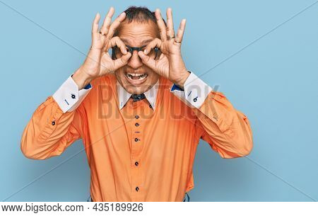Middle age indian man wearing casual clothes and glasses doing ok gesture like binoculars sticking tongue out, eyes looking through fingers. crazy expression.