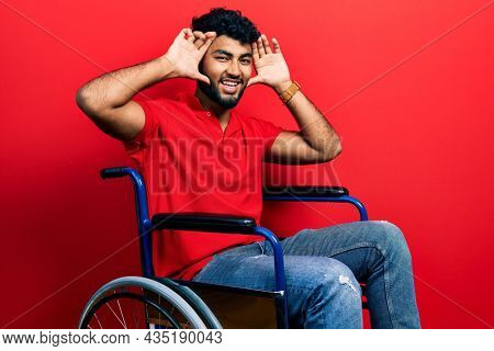 Arab man with beard sitting on wheelchair smiling cheerful playing peek a boo with hands showing face. surprised and exited
