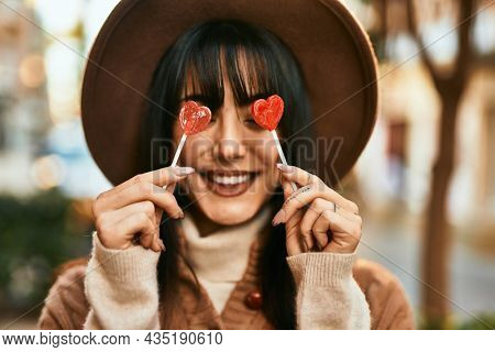 Brunette woman wearing winter hat being funny holding lollipops covering eyes outdoors at the city