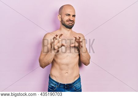 Young bald man standing shirtless disgusted expression, displeased and fearful doing disgust face because aversion reaction. with hands raised