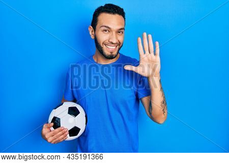 Hispanic man with beard holding soccer ball waiving saying hello happy and smiling, friendly welcome gesture