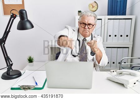 Senior caucasian man wearing doctor uniform and stethoscope at the clinic punching fist to fight, aggressive and angry attack, threat and violence