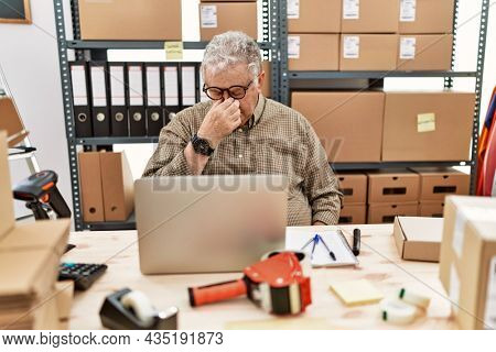 Senior caucasian man working at small business ecommerce with laptop tired rubbing nose and eyes feeling fatigue and headache. stress and frustration concept.