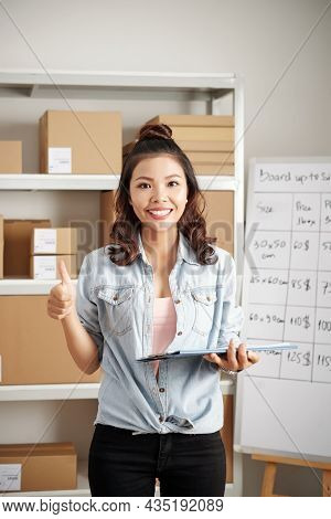 Portrait Of Happy Young Asian Postal Worker With Curly Hair Holding Folder With Documents And Showin