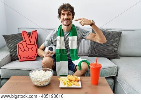 Young hispanic man football hooligan cheering game at home smiling cheerful showing and pointing with fingers teeth and mouth. dental health concept.