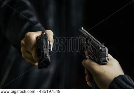 Two Persons Hands With Weapons Pointed At Each Other. Shootout With Firearms Of Two Criminals. Kille