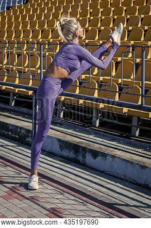 Sexy Woman Stretching Outdoor. Athletic Woman In Sportswear Training On Stadium. Warming Up Her Musc