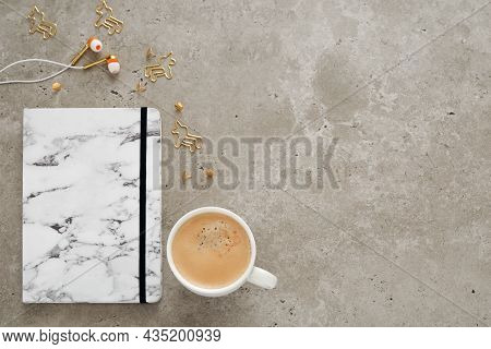 Top View Of Desk With Notepad, Coffee Cup, Earphones, Pen And Staples. Flat Lay, Free Space For Text