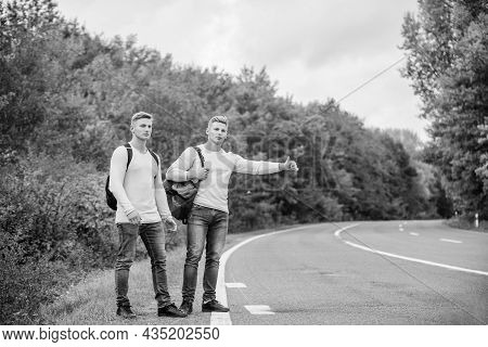 Type Of Adventure. On The Road. Enjoying Summer Hike. Looking For Transport. Twins Walking Along Roa