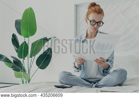 Casually Dressed Young Woman In Spectacles Holding Financial Papers Bills In Hands While Sitting On