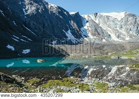 Snowy Mountain Reflected In Clear Water Of Glacial Lake. Beautiful Sunny Landscape With Glacier Refl