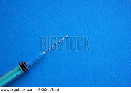 A Syringe With A Needle Rests On A Blue Background. Vaccination, Injection, Injection, Treatment, An