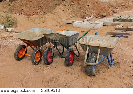 Construction Wheelbarrows. Three Wheelbarrows Without People On The Construction Site. Construction