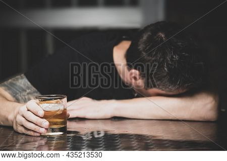 Drunk Man Sleeping At A Bar Table With A Glass Of Whiskey In Hand
