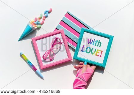Text With Love In Picture Frame In Hand. Sweets And Vibrant Party Decor Objects. Candy, Snacks, Funn