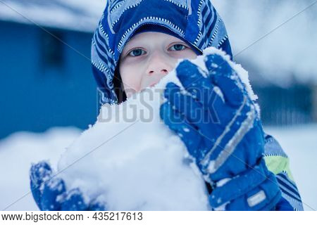 Boy In Winter Overalls Stands On Outdoors And Eats Snow Holding Large Lump Of Snow In His Hands