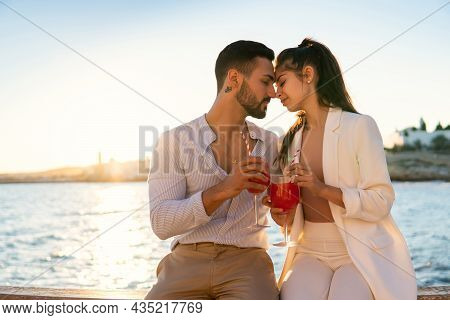 Loving Hispanic Couple With Glasses Of Cocktails Sitting Face To Face On Embankment And Touching Nos