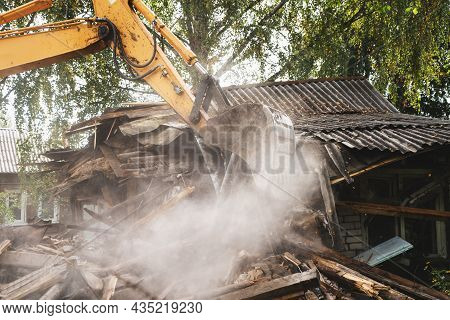 Excavator Bucket Breaks Old House. Building Demolition. Structure Dismantling.