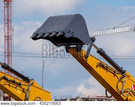 Lifted Bucket Of New Excavator Against The Background Of The Construction Site. Close-up Of New Cons