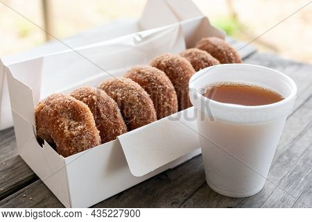Cup Of Apple Cider And Half Dozen Of Cinnamon Donuts On Wooden Table