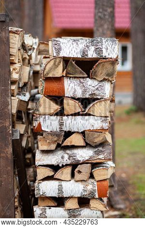 Firewood Background Of Chopped Wood For Kindling And Heating The House Close-up. A Woodpile With Sta