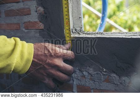 Hand Of Man Using Tape Measure Window With Brick Wall Background. Construction Workers Work At Const