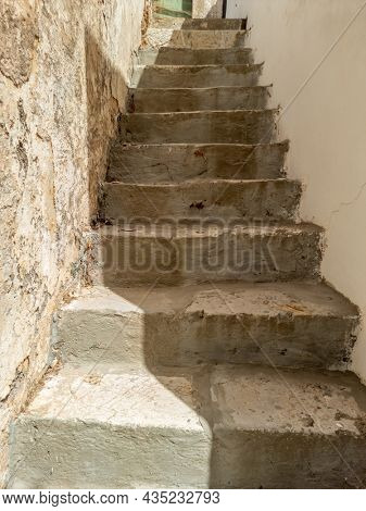 Empty narrow stonestairs on exterior, between stonewall and house