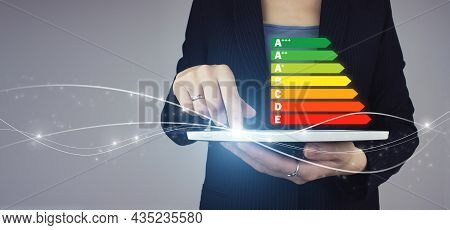 Model Of Energy Efficiency Rate. White Tablet In Businesswoman Hand With Digital Hologram Energy Eff