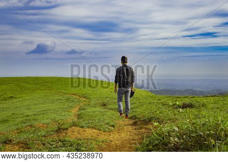 A Backpacker Walking On A Hill With Blue Sky And Copy Space, Man Backpacking On A Hill And Blue Sky