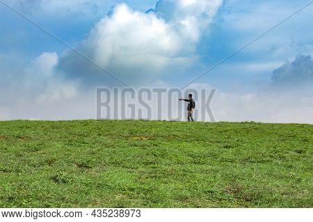 A Backpacker On A Hill With Blue Sky And Copy Space, Man Backpacking On A Green Hill With Copy Space