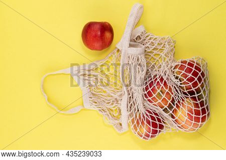 Mesh Shopping Bag With Organic Apples Fruit On Yellow Background. Caring For The Environment.zero Wa